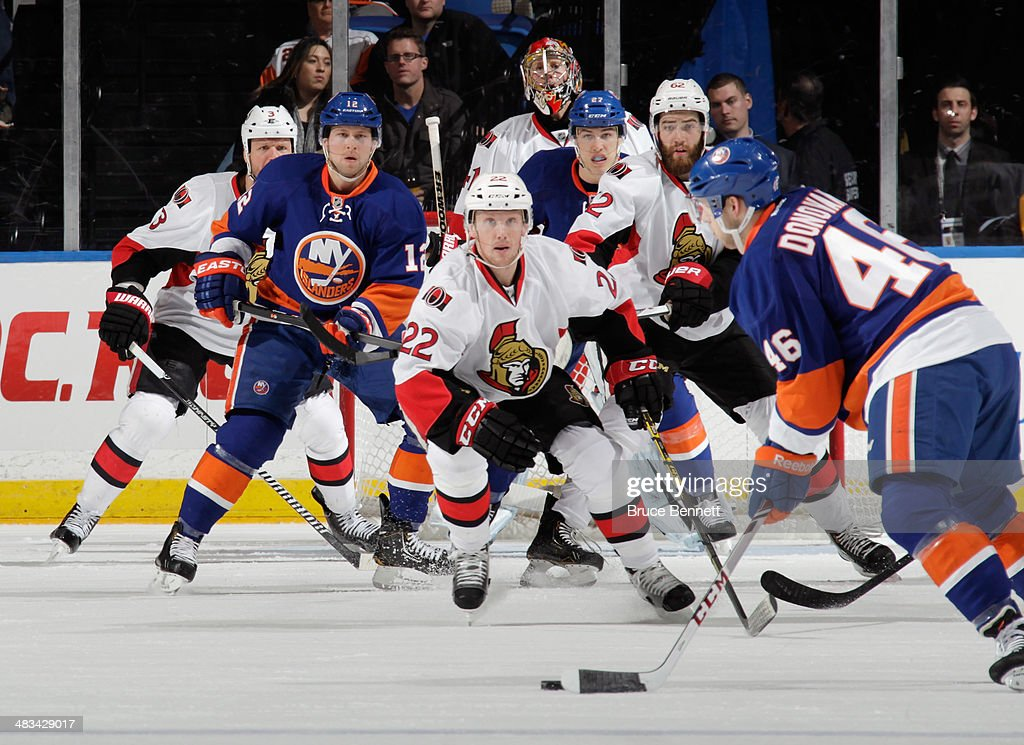 Erik Condra #22 of the Ottawa Senators defends Matt Donovan #46 of the New York Islanders in the first period at the Nassau Veterans Memorial Coliseum on April 8, 2014 in Uniondale, New York.