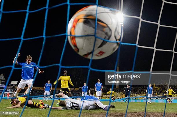 Erik Durm of Dortmund scores his team's second goal past Marcel Heller of Darmstadt and goalkeeper Christian Mathenia of Darmstadt during the...