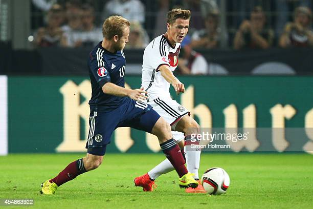 Erik Durm of Germany is challenged by Barry Bannan of Scotland during the EURO 2016 Qualifier match between Germany and Scotland at Signal Iduna Park...