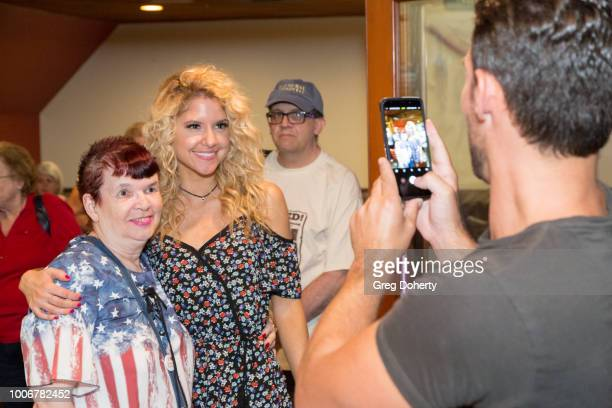 Erik Fellows Brittany Underwood takes a picture with a fan at The Bay Cast Host Fan Appreciation Event on July 27 2018 in Glendale California