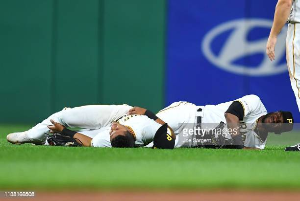 Erik Gonzalez and Starling Marte of the Pittsburgh Pirates are injured after colliding during the eighth inning against the San Francisco Giants at...