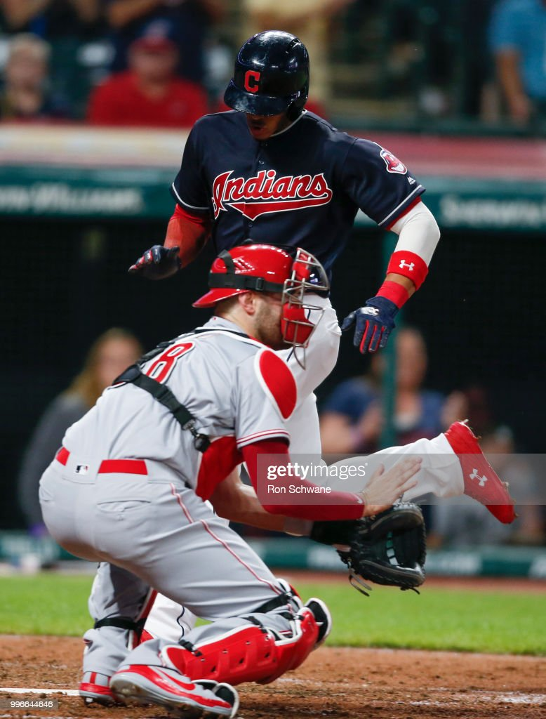 Erik Gonzalez #9 of the Cleveland Indians scores past Curt Casali #38 of the Cincinnati Reds on a single by Yonder Alonso #17 during the seventh inning at Progressive Field on July 11, 2018 in Cleveland, Ohio.