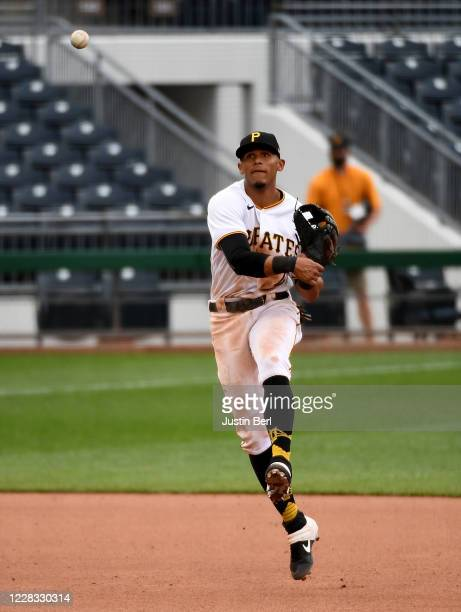 Erik Gonzalez of the Pittsburgh Pirates commits a throwing error while attempting to force out Cameron Maybin of the Chicago Cubs in the ninth inning...