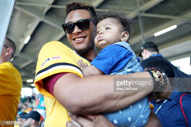 Erik Gonzalez of the Pittsburgh Pirates holds a baby in the stand at Howard J. Lamade Stadium prior to the Little League Classic between the Chicago...