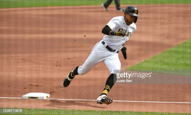 Erik Gonzalez of the Pittsburgh Pirates rounds third base as he heads home to score a run on an RBI single by Adam Frazier in the first inning during...
