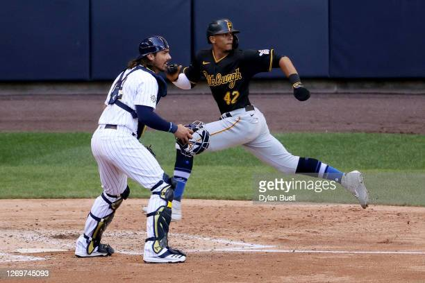 Erik Gonzalez of the Pittsburgh Pirates scores a run past Jacob Nottingham of the Milwaukee Brewers in the fifth inning at Miller Park on August 30,...