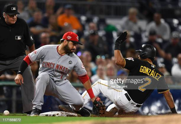 Erik Gonzalez of the Pittsburgh Pirates slides safely into third base in front of Eugenio Suarez of the Cincinnati Reds during the fifth inning at...