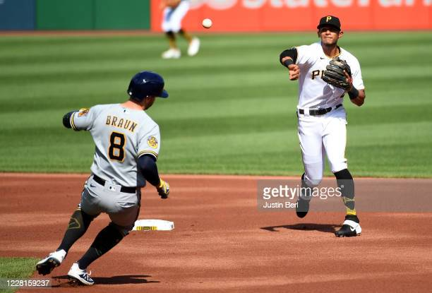 Erik Gonzalez of the Pittsburgh Pirates turns a double play against Ryan Braun of the Milwaukee Brewers in the first inning during the game at PNC...
