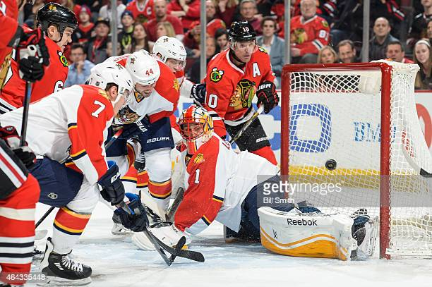 Erik Gudbranson of the Florida Panthers and Patrick Sharp of the Chicago Blackhawks watch the puck get past goalie Roberto Luongo to give the...