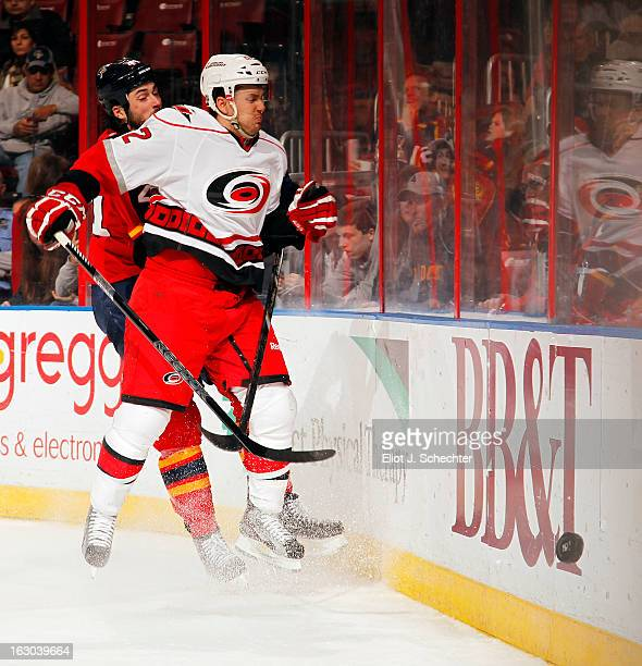 Erik Gudbranson of the Florida Panthers checks Brett Sutter of the Carolina Hurricanes into the boards during the second period at the BB&T Center on...