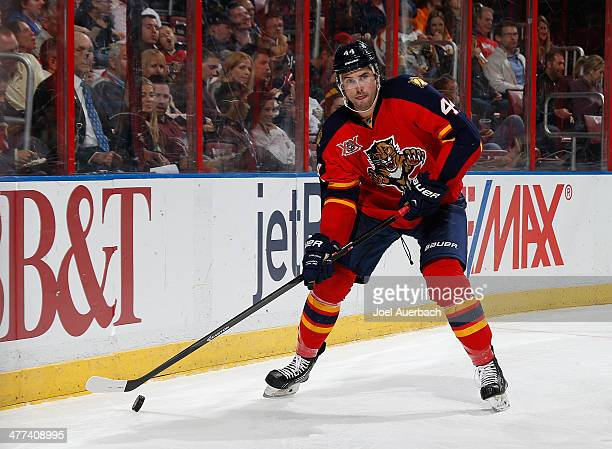 Erik Gudbranson of the Florida Panthers circles the net with the puck against the Buffalo Sabres at the BBT Center on March 7 2014 in Sunrise Florida...