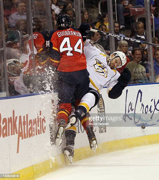 Erik Gudbranson of the Florida Panthers hits Paul Gaustad of the Nashville Predators into the boards at the BankAtlantic Center on March 3 2012 in...