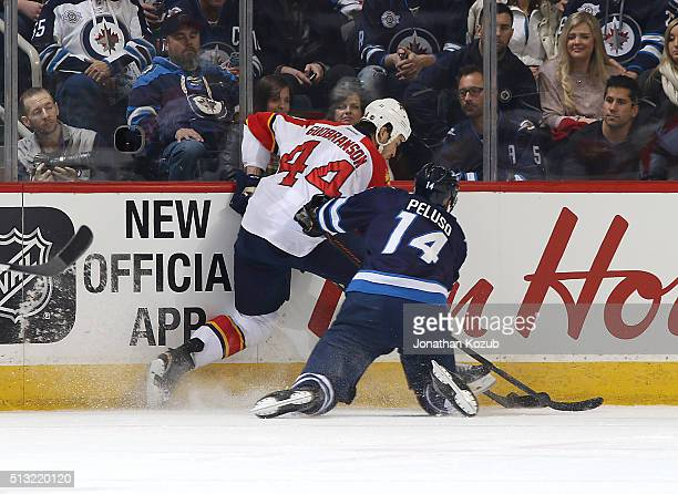 Erik Gudbranson of the Florida Panthers keeps the puck away from Anthony Peluso of the Winnipeg Jets as they battle along the boards during first...