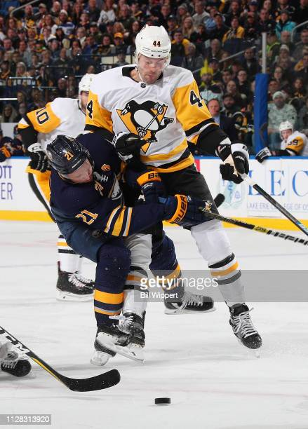 Erik Gudbranson of the Pittsburgh Penguins delivers a hit to Kyle Okposo of the Buffalo Sabres during an NHL game on March 1 2019 at KeyBank Center...