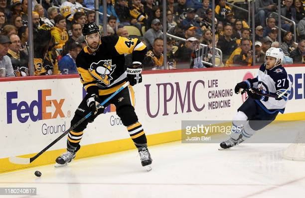 Erik Gudbranson of the Pittsburgh Penguins skates with the puck in the first period during the game against the Winnipeg Jets at PPG PAINTS Arena on...