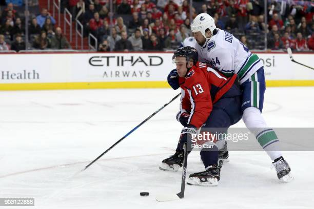 Erik Gudbranson of the Vancouver Canucks and Jakub Vrana of the Washington Capitals go after the puck in the second period at Capital One Arena on...