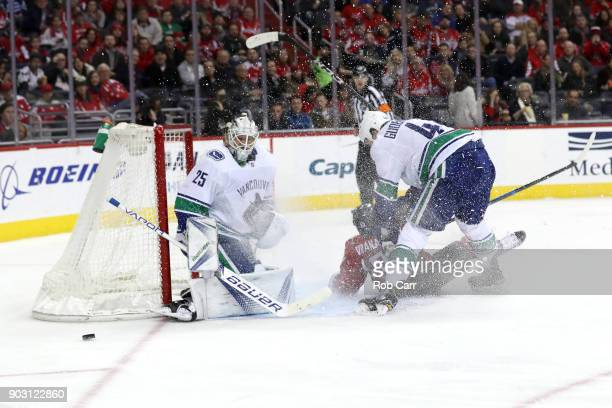 Erik Gudbranson of the Vancouver Canucks and Jakub Vrana of the Washington Capitals go after the puck as goalie Jacob Markstrom looks on the second...