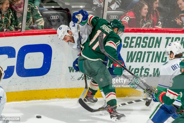 Erik Gudbranson of the Vancouver Canucks and Zach Parise of the Minnesota Wild battle for the puck during the game at the Xcel Energy Center on...