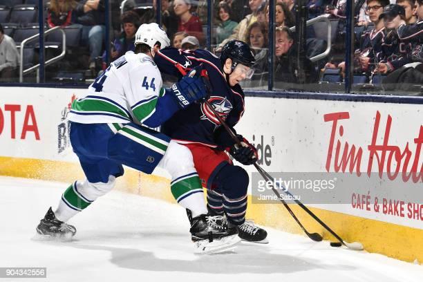 Erik Gudbranson of the Vancouver Canucks attempts to knock Matt Calvert of the Columbus Blue Jackets off the puck during the first period of a game...