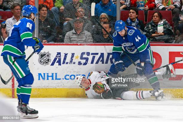 Erik Gudbranson of the Vancouver Canucks checks John Hayden of the Chicago Blackhawks during their NHL game at Rogers Arena December 28 2017 in...