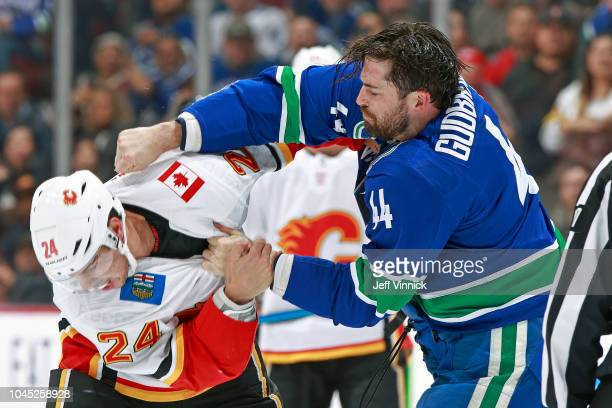 Erik Gudbranson of the Vancouver Canucks fights Travis Hamonic of the Calgary Flames during their NHL game at Rogers Arena October 3 2018 in...