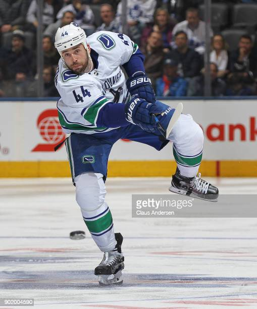 Erik Gudbranson of the Vancouver Canucks fires a puck in against the Toronto Maple Leafs during an NHL game at the Air Canada Centre on January 6...