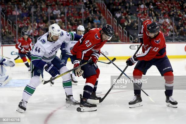Erik Gudbranson of the Vancouver Canucks goes for the puck against Tom Wilson and Jakub Vrana of the Washington Capitals at Capital One Arena on...