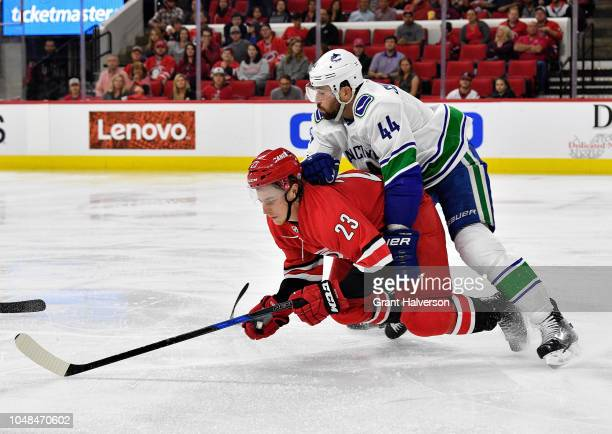 Erik Gudbranson of the Vancouver Canucks knocks Brock McGinn of the Carolina Hurricanes to the ice during their game at PNC Arena on October 9 2018...