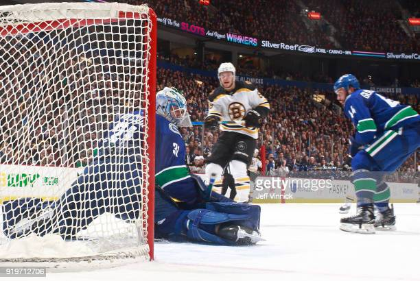Erik Gudbranson of the Vancouver Canucks looks on as Anders Nilsson of the Vancouver Canucks m makes a save off the shot of David Pastrnak of the...