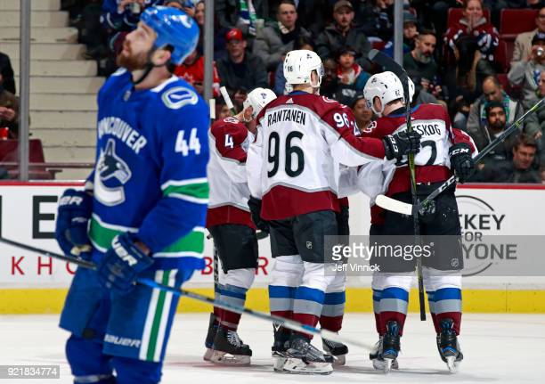 Erik Gudbranson of the Vancouver Canucks looks on as Tyson Jost of the Colorado Avalanche is congratulated by teammates after scoring during their...