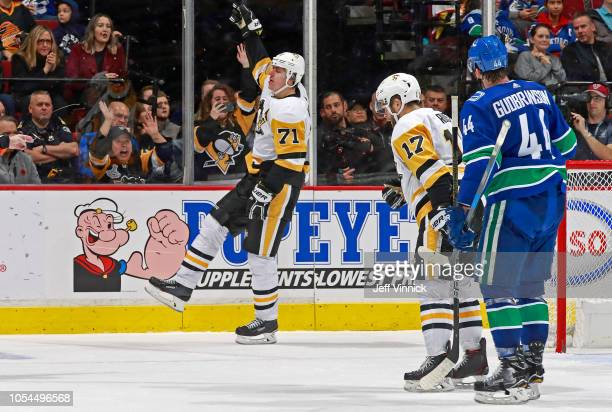 Erik Gudbranson of the Vancouver Canucks looks on dejected as Evgeni Malkin of the Pittsburgh Penguins celebrates after scoring during their NHL game...