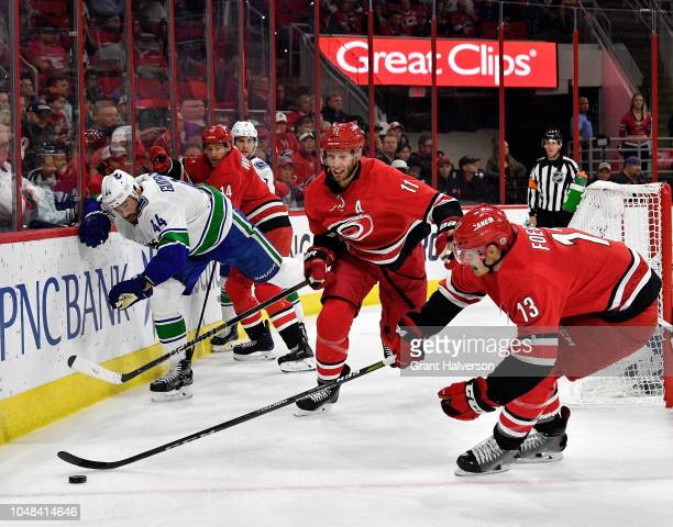 Erik Gudbranson of the Vancouver Canucks loses his stick as Jordan Staal and Warren Foegele of the Carolina Hurricanes track down a loose puck during...