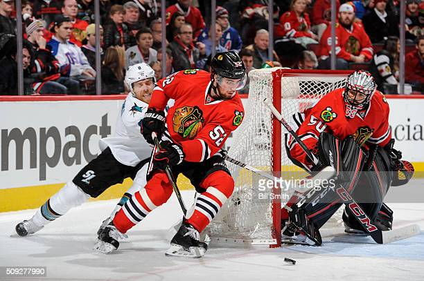 Erik Gustafsson of the Chicago Blackhawks and Joe Pavelski of the San Jose Sharks chase the puck around the net guarded by goalie Corey Crawford in...