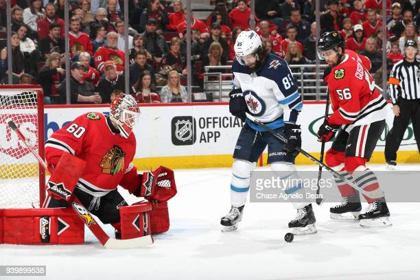 Erik Gustafsson of the Chicago Blackhawks and Mathieu Perreault of the Winnipeg Jets watch the puck in front of goalie Collin Delia in the second...