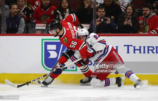 Erik Gustafsson of the Chicago Blackhawks and Mika Zibanejad of the New York Rangers battle along the boards for the puck at the United Center on...