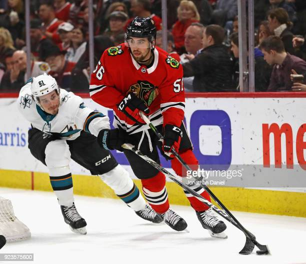 Erik Gustafsson of the Chicago Blackhawks looks to pass under pressure from Justin Braun of the San Jose Sharks at the United Center on February 23...