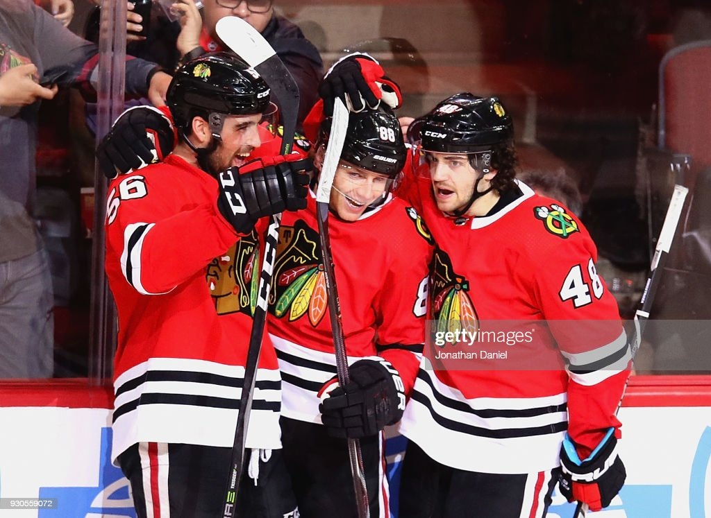 Erik Gustafsson #56, Patrick Kane #88 and Vinnie Hinostroza #48 of the Chicago Blackhawks celebrate Kanes' third period goal against the Boston Bruins at the United Center on March 11, 2018 in Chicago, Illinois. The Blackhawks defeated the Bruins 3-1.
