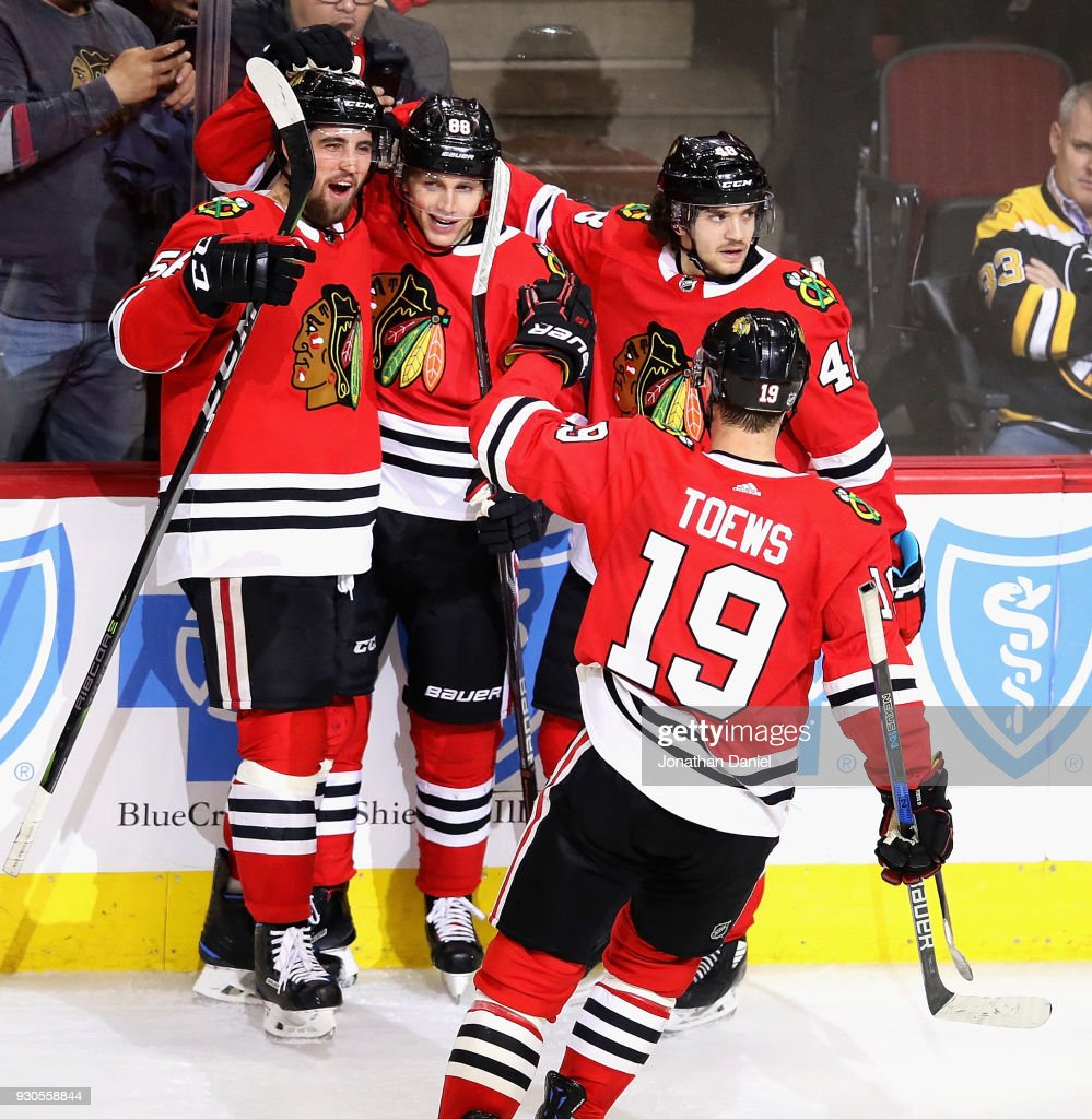 Erik Gustafsson #56, Patrick Kane #88, Vinnie Hinostroza #48 and Jonathan Toews #19 of the Chicago Blackhawks celebrate Kanes' third period goal against the Boston Bruins at the United Center on March 11, 2018 in Chicago, Illinois. The Blackhawks defeated the Bruins 3-1.