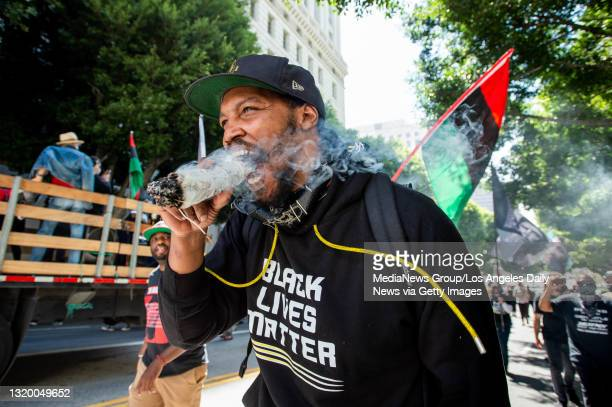 Erik Hardeman burns sage to peacefully cleanse the area during a Black Lives Matter march through downtown Los Angeles on the first anniversary of...