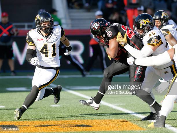 Erik Harris moves into help Arnaud GasconNadon of the Hamilton TigerCats tackle William Powell of the Ottawa REDBLACKS during the CFL Eastern Final...
