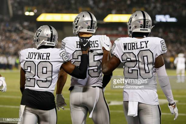 Erik Harris of the Oakland Raiders celebrates with Lamarcus Joyner and Daryl Worley after scoring an touchdown on an interception thrown by Philip...