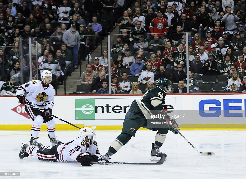 Erik Haula #56 of the Minnesota Wild controls the puck against Niklas Hjalmarsson #4 and Johnny Oduya #27 of the Chicago Blackhawks during the second period in Game Six of the Second Round of the 2014 NHL Stanley Cup Playoffs on May 13, 2014 at Xcel Energy Center in St Paul, Minnesota. The Blackhawks defeated the Wild 2-1 in overtime.