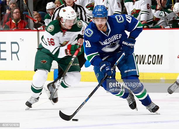 Erik Haula of the Minnesota Wild looks on as Brandon Sutter of the Vancouver Canucks skates up ice with the puck during their NHL game at Rogers...
