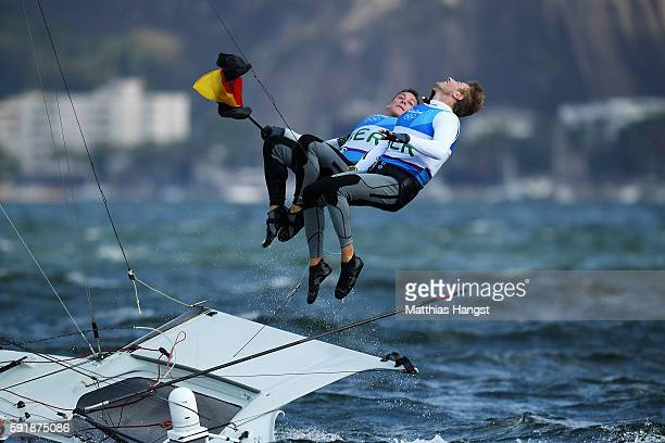 Erik Heil of Germany and Thomas Ploessel of Germany celebrate by jumping in the sea after winning the bronze medal in the Men's 49er class at the...