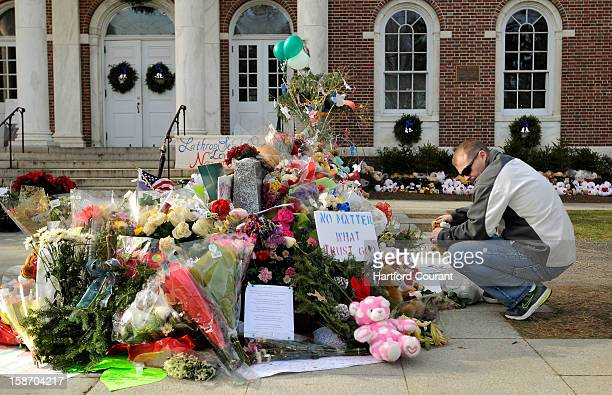 Erik Johannsen of Dover Maryland places stuffed animals at a memorial Monday December 24 to honor the 26 people killed in the Sandy Hook Elementary...