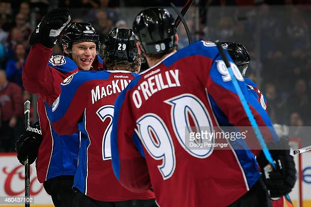 Erik Johnson of the Colorado Avalanche celebrates his goal against the St Louis Blues with teammates Nathan MacKinnon and Ryan O'Reilly to tie the...