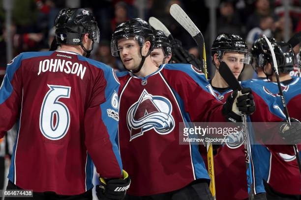 Erik Johnson of the Colorado Avalanche is congratulated by Cody Goloubef after scoring the winning goal against the Chicago Blackhawks at the Pepsi...
