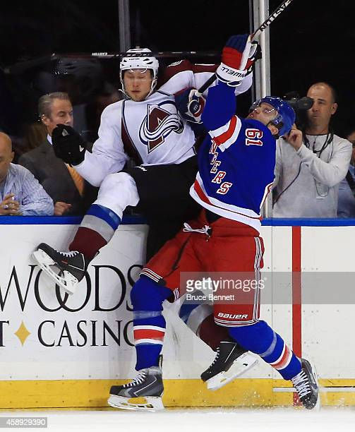Erik Johnson of the Colorado Avalanche is hit into the boards by Rick Nash of the New York Rangers during the first period at Madison Square Garden...