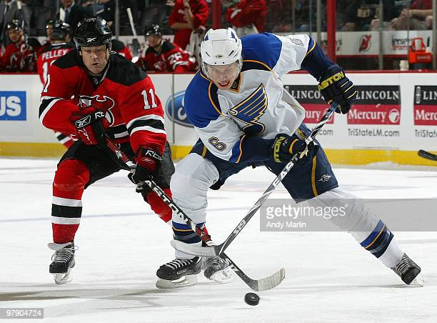 Erik Johnson of the St Louis Blues and Dean McAmmond of the New Jersey Devils battle for a loose puck during the game at the Prudential Center on...