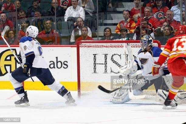 Erik Johnson shoots the puck into his own goal as Ty Conklin of the St. Louis Blues reacts during the first period against the Calgary Flames on...